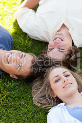 Three students resting together while looking at camera