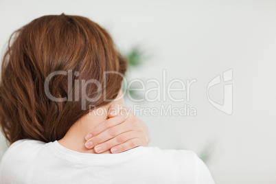 Close up of a brunette woman massing her neck