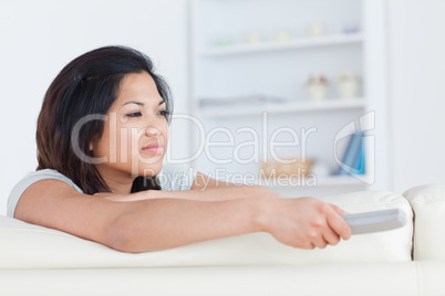 Woman pressing on a television remote while sitting on a white c