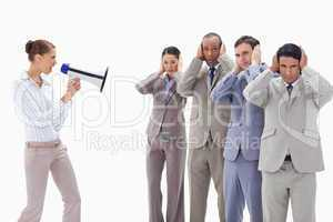 Woman yelling through a megaphone at business people covering th