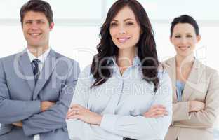 Young smiling executive woman crossing her arms in front of two