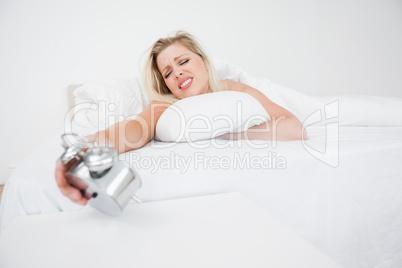 Upset woman looking at her alarm clock