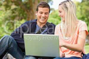 Laughing young people sitting while using a laptop