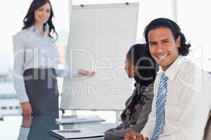 Smiling employee listening to the presentation given by a collea