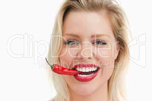 Happy woman biting a red chili while standing