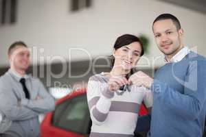Happy couple holding keys together