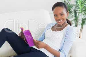 Black woman sitting on a sofa while holding a book