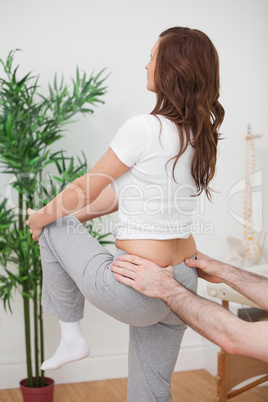 Woman stretching her leg while a man is touching her back