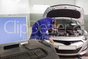 Mechanic repairing a car next to a computer
