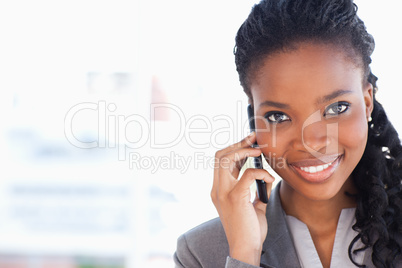Young smiling businesswoman looking ahead while talking on a pho