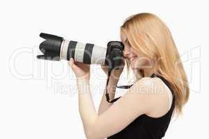 Woman smiling while holding a SLR camera