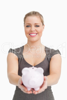 Piggy bank showing by a pretty woman