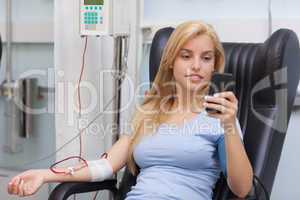 Blood donor looking at her mobile phone