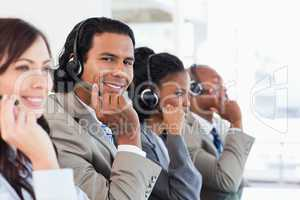 Young call centre employee working among his team