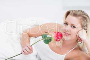 Young woman holding a pink rose