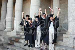 Five happy graduates posing the arms raised