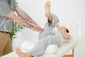 Woman stretching her leg while a man is massaging her