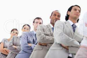 Low-angle shot of people dressed in suits crossing their arms in