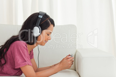 Young Latino listening music with her smartphone