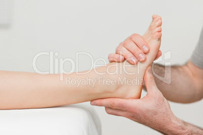Hands of an osteopath massaging a foot