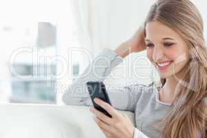 A smiling girl looking at her mobile phone