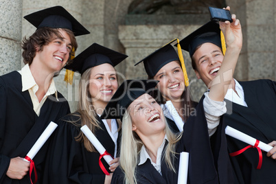 Close-up of happy graduates taking a picture of themselves
