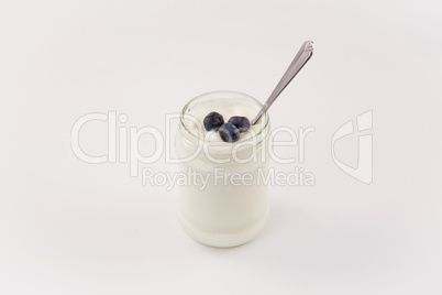Pot of yoghurt with three blueberries
