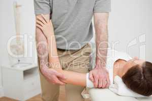 Physiotherapist pressing the shoulder of a woman
