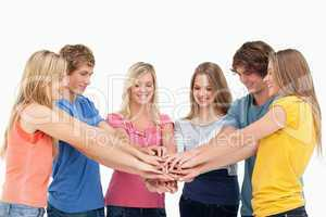 Friends standing around each other as they stack their hands and