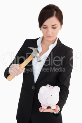 Woman in suit  going to break a piggy-bank