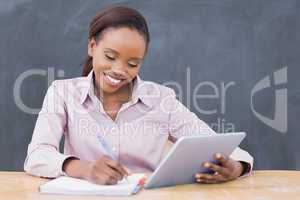 Teacher smiling while holding a tablet computer