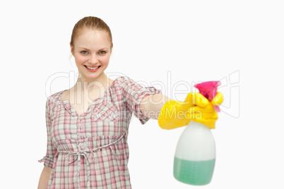 Joyful woman holding a spray bottle while smiling
