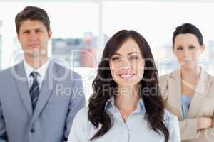Young smiling woman standing in front of two co-workers