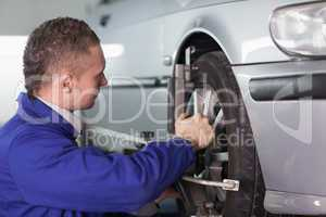 Concentrated mechanic repairing a car wheel