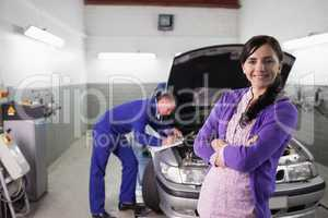 Woman smiling with arms crossed next to a mechanic