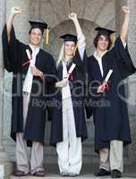 Smiling graduates raising arm