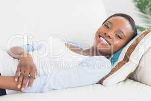 Black woman lying on back on a sofa