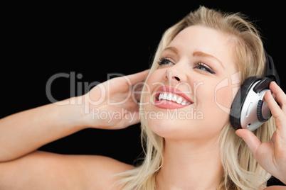 Cheerful blonde woman wearing headphones