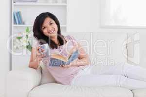 Smiling woman holding a book and a mug while lying on a couch