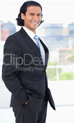 Businessman wearing a suit and standing upright in a well-lit ro