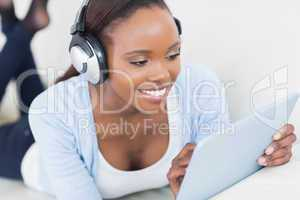 Black woman lying on front using a table computer