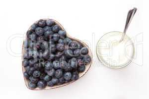 White yogurt and blueberries in a heart shaped bowl
