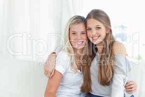 A pair of sisters hug each other as they look into the camera