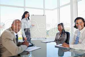 Smiling businesswoman giving a presentation to her relaxed colle