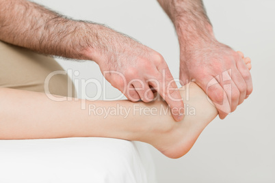 Hands of a physiotherapist massaging the foot of a patient