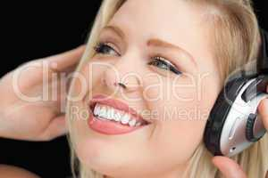 Happy blonde woman listening to music through headphones