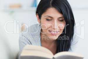 Woman smiles as she holds a book on a couch
