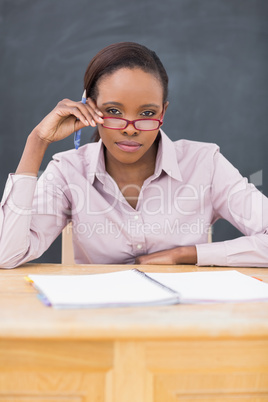 Teacher sitting at desk while touching her glasses