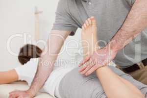 Physiotherapist bending the leg of his peaceful patient