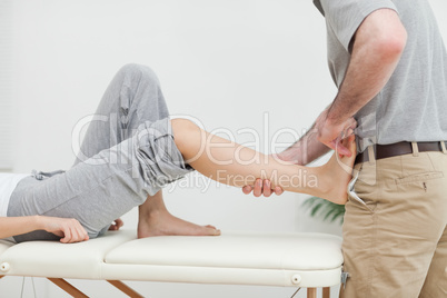 Close-up of a physiotherapist stretching the foot of a patient